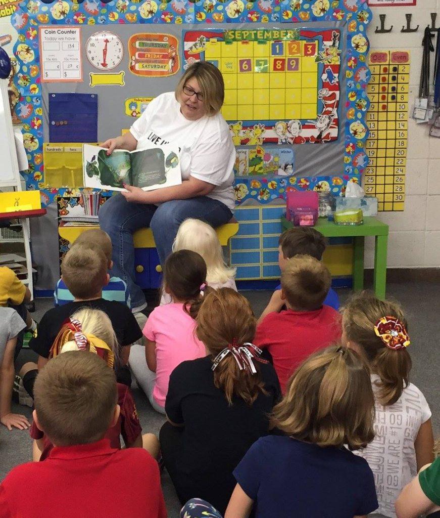 Cheri enjoying a book helping Raising Readers.